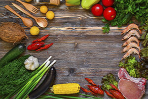 Diverse Gemüse, Shrimps und Fleisch, die kreisförmig auf einem Holzbrett angeordnet sind.