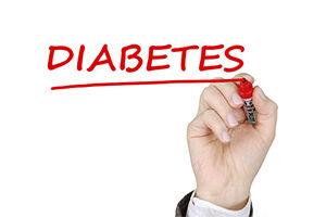 """Eine mit der Handfläche dem Betrachter zugewandte Hand schreibt mit Rotstift in Majuskeln das Wort """"Diabetes"""" an eine Glasscheibe, sodass es für den Leser lesbar ist."""