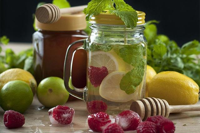 Glas gefüllt mit Wasser und darin schwimmend Zitronenscheiben, Zitronenmelisse, und eine Himbeere. Verteilt um das Glas herum liegen weitere Himbeeren, zum Teil gefrostet in Eiswürfeln, Limetten, Zitronen, ein Mörser und Zitronenmelisse.