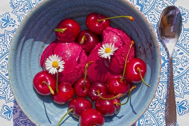 Dessertschale mit rotem Fruchtsorbet, Kirschen und Gänseblümchen verziert, auf einer blaugemusterten weißen Tischdecke, mit Löffel bereit zum Naschen, daneben.