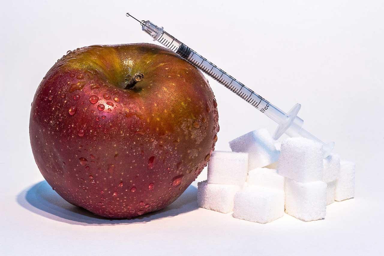 Neben einem Apfel iegen mehrere Zuckerwürfel. Darüber drapiert ist eine Spritze.