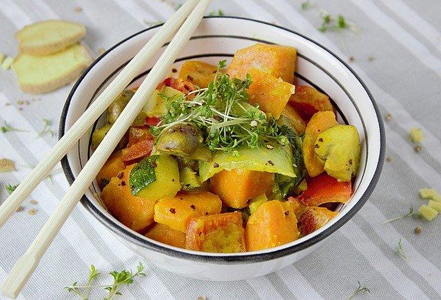 Schüssel mit Süßkartoffeln und Essstäbchen oben auf dem Rand liegend